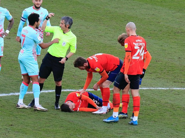 Dan Potts stays down after suffering a head injury against Swansea
