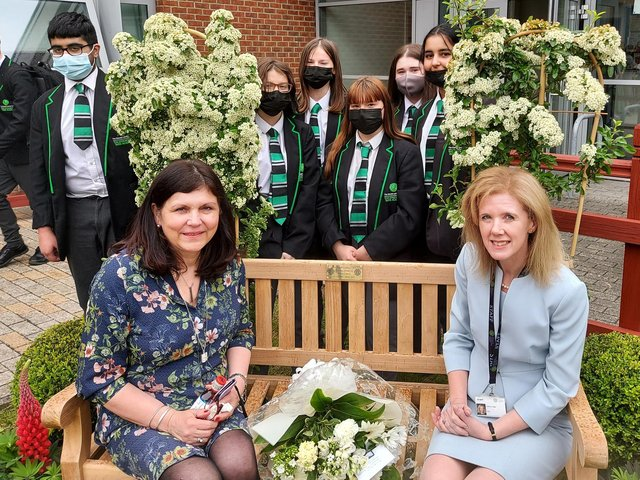 Yolanda Lewis and Cathy Barr, CEO of the Shared Learning Trust, at the memorial bench with several pupils taught by Mr Lewis